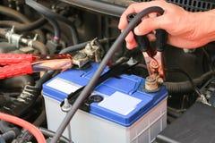 Os cabos da ligação em ponte da bateria dos usos do mecânico de carro carregam uma bateria inoperante fotos de stock