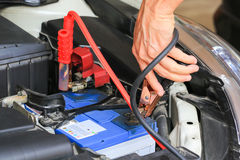 Os cabos da ligação em ponte da bateria dos usos do mecânico de carro carregam uma bateria inoperante imagem de stock royalty free