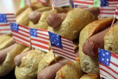 Os cachorros quentes americanos com as bandeiras americanas pequenas fecham o plano, o bolo e a salsicha imagens de stock royalty free