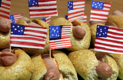 Os cachorros quentes americanos com as bandeiras americanas pequenas fecham o plano, o bolo e a salsicha foto de stock