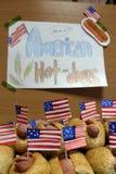 Os cachorros quentes americanos com as bandeiras americanas pequenas fecham o plano, o bolo e a salsicha e cachorros quentes amer Fotografia de Stock Royalty Free