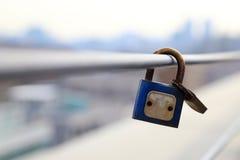 Os cadeado dos pares são fechados no trilho com fundo borrado da cidade, Fotografia de Stock Royalty Free