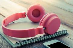 Os cadernos e os smartphones sobre postos cor-de-rosa do fone de ouvido na manhã de madeira do assoalho iluminam-se Foto de Stock