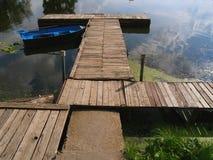 Os cais de madeira do cais na lagoa e do barco velho azul na superfície da água Imagens de Stock