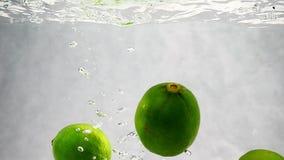 Os cais verdes são jogados em um recipiente da água Vídeo do fruto no movimento lento video estoque