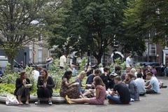 Os caixeiros de escritório sentam-se na grama e jantam-se no quadrado dourado, Soho, expondo as caras ao sol Imagens de Stock