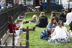Os caixeiros de escritório sentam-se na grama e jantam-se no quadrado dourado, Soho, expondo as caras ao sol Fotos de Stock Royalty Free