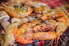 Os camarões e os calamares grelhados no fogão do carvão vegetal na noite party Sea Foto de Stock