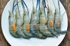 Os camarões frescos em uma placa branca na natureza de madeira da tabela iluminam-se Foto de Stock