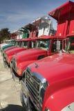 Os caminhões basculantes vermelhos brilhantes da capa de chuva alinham a estrada em seguido, em Maine perto da beira de New Hamps Foto de Stock Royalty Free