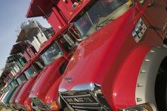 Os caminhões basculantes vermelhos brilhantes da capa de chuva alinham a estrada em seguido, em Maine perto da beira de New Hamps Foto de Stock