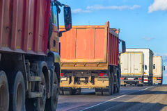 Os caminhões e os caminhões basculantes vão na estrada Foto de Stock
