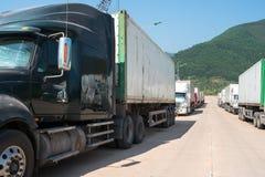 Os caminhões pesados carregaram com os reboques dos bens, estacionados na área de espera na passagem fronteiriça do estado em Vie imagem de stock royalty free
