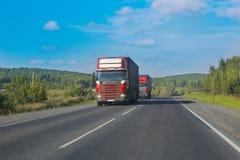 Os caminhões vão na estrada Foto de Stock