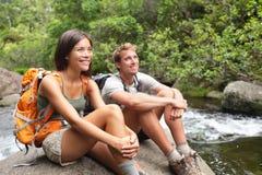 Os caminhantes acoplam o relaxamento pelo rio Fotos de Stock Royalty Free