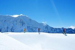 Os caminhantes com trouxas alcançam a cimeira do pico de montanha Liberdade do sucesso e realização da felicidade nas montanhas E fotos de stock royalty free