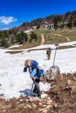 Os caminhantes dos homens que levam trouxas andam na rota ao longo do passeio do turista em montanhas caucasianos na primavera Fotografia de Stock