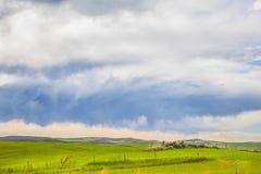 Os campos verdes com céus nebulosos ajardinam foto de stock royalty free