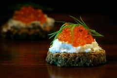Os Canapes com o caviar vermelho com aneto decoram na madeira do marrom escuro Imagens de Stock