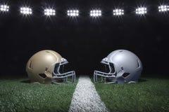 Os capacetes de futebol que enfrentam fora em uma linha de jardas abaixo do estádio iluminam-se Imagem de Stock Royalty Free