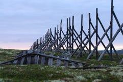Os cargos de madeira velhos da cerca na neve atrasam nos montes Imagens de Stock Royalty Free