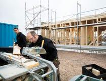 Os carpinteiros que cortam a madeira que usa a tabela viram no local Imagem de Stock Royalty Free