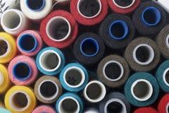 Os carretéis das linhas de cores diferentes são dobrados em uma caixa Linhas de cores diferentes Acessórios para costurar e borda Imagem de Stock