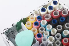 Os carretéis das linhas de cores diferentes são dobrados em uma caixa Linhas de cores diferentes Acessórios para costurar e borda Fotografia de Stock