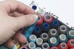 Os carretéis das linhas de cores diferentes são dobrados em uma caixa Uma das bobinas que o homem toma fora da caixa Acessórios p Foto de Stock
