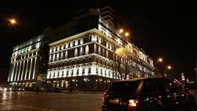 Os carros aproximam a construção com iluminação da noite filme