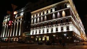 Os carros aproximam a construção com iluminação da noite em Kiev, Ucrânia vídeos de arquivo