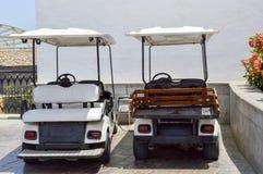 Os carros bondes brancos do golfe são estacionados em veículos elétricos pequenos com os toldos do sol em um exótico do sul tropi fotografia de stock royalty free