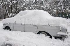 Os carros, cobertos com a camada grossa de neve, na jarda da casa residencial na cidade provilcial imagem de stock royalty free