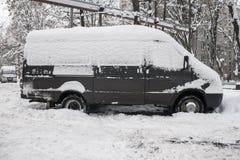 Os carros, cobertos com a camada grossa de neve, na jarda da casa residencial na cidade provilcial fotografia de stock royalty free