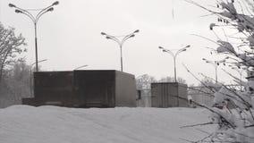 Os carros conduzem em uma estrada de cidade do inverno atr?s de um monte de neve Parte 1 filme