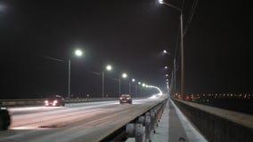 Os carros conduzem sobre a ponte da neve na noite filme