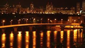 Os carros da cidade do sono da noite conduzem na reflexão da luz amarela da ponte vídeos de arquivo