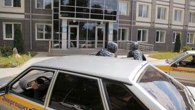Os carros de empresa da segurança conduzem acima aos indivíduos de construção com as armas corridas ao escritório vídeos de arquivo