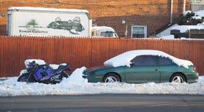Os carros e a motocicleta sob a neve em Brooklyn após tempestades maciças do inverno golpeiam para o nordeste Foto de Stock Royalty Free
