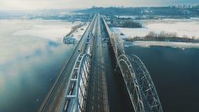 Os carros e o trem movem-se em uma ponte sobre uma metragem aérea congelada do zangão do rio vídeos de arquivo