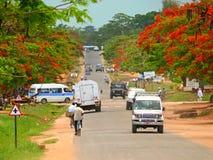 Os carros e os homens em bicicletas vão na estrada Fotografia de Stock