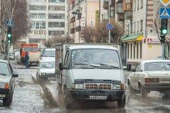 Os carros espirram através da grande poça na rua inundada Imagens de Stock