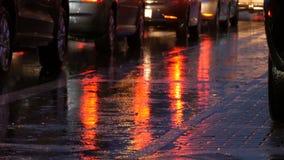 Os carros estão no tráfego, faróis na chuva no asfalto, vista abaixo A chuva bate as poças na noite Reflexão do carro filme