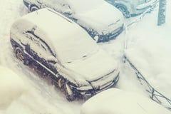 Os carros estacionados nevaram durante uma queda de neve Imagens de Stock