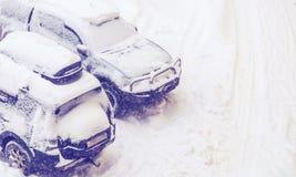 Os carros estacionados nevaram durante uma queda de neve Foto de Stock
