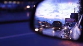 Os carros movem-se na manhã do dia, refletida no espelho de um outro carro filme