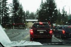 Os carros na luz da parada molharam e estrada nevado Imagem de Stock Royalty Free