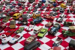 Os carros pequenos coloridos do brinquedo colocaram na tela vermelha e branca no mercado de Flohmarkt im Mauerpark em Berlim Fotografia de Stock Royalty Free