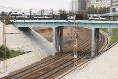 Os carros são colados no tráfego em uma ponte da estrada sobre a estrada de ferro com rede da fonte elétrica do contato em Novosi Imagem de Stock