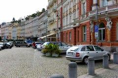 Os carros são estacionados ao lado das casas de cortiço fotos de stock